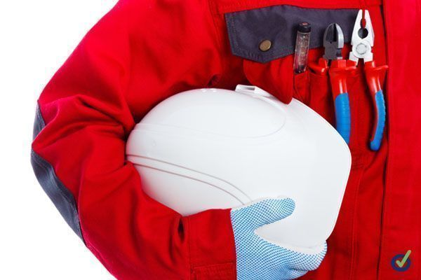 Maintenance technician in workwear holding his protective helmet.